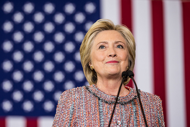 image of Hillary Clinton grinning cheekily in front of a U.S. flag