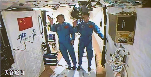 Jing Haipeng (left) and Chen Dong (right) wave to ground controllers after entering Tiangong-2. Photo Credit: Xinhua