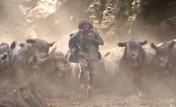 Moose Finbar (Kevin Hart) tries to outrun a horde of (CGI) rhinos in JUMANJI: WELCOME TO THE JUNGLE (2017)