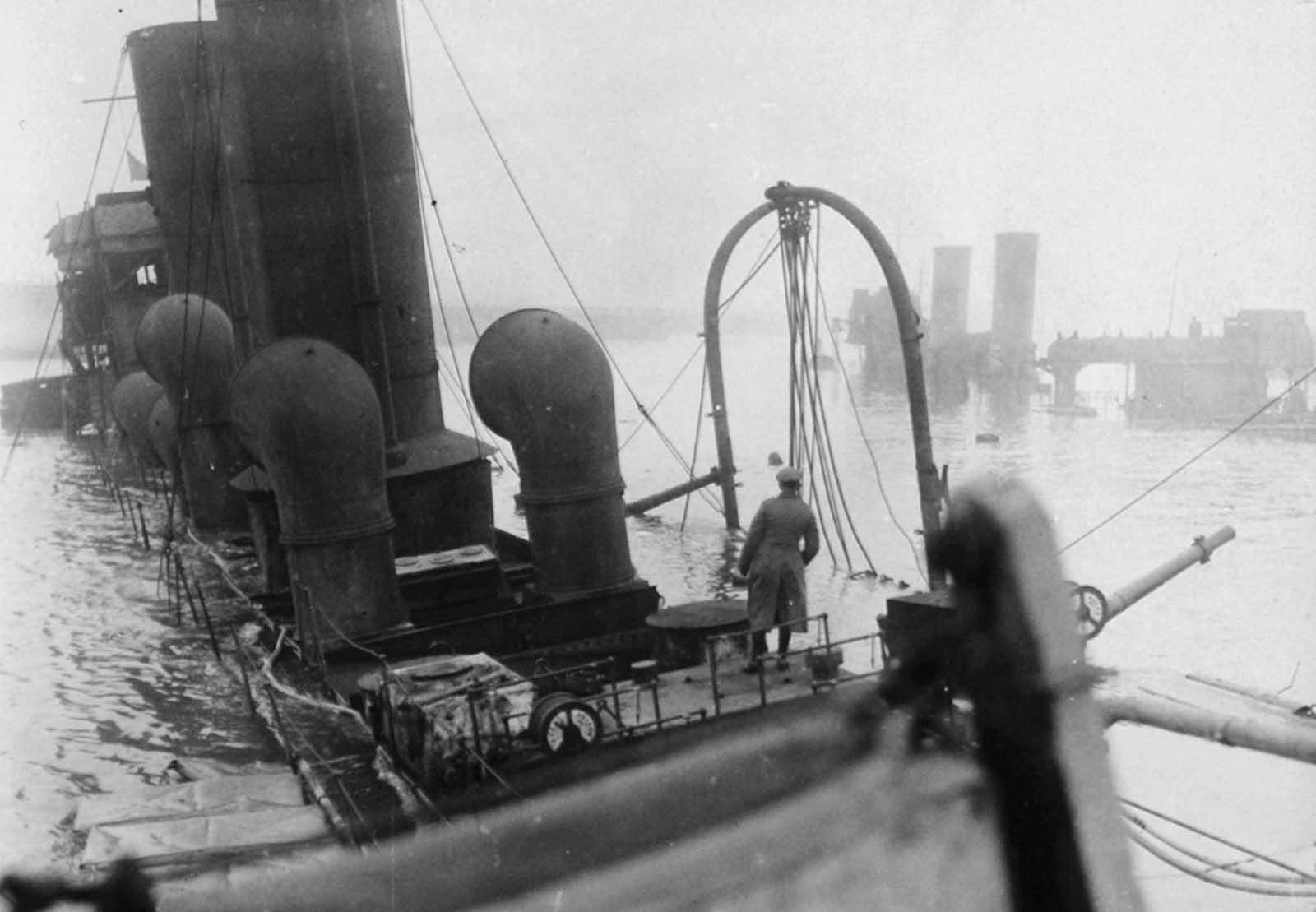 A Zeebrugge Raid-re 1918. április 23-án került sor. A Királyi Haditengerészet megkísérelte blokkolni a belgiumi Bruges-Zeebrugge kikötőt azáltal, hogy régebbi hajókat süllyesztett a csatorna bejáratánál, hogy megakadályozzák a német hajók elhagyását a kikötőből.  Két hajót süllyedt el a csatornába 583 ember életére.  Sajnos a hajókat rossz helyre süllyedték el, és a csatornát napokban újra kinyitották.  A fénykép 1918 májusában készült.