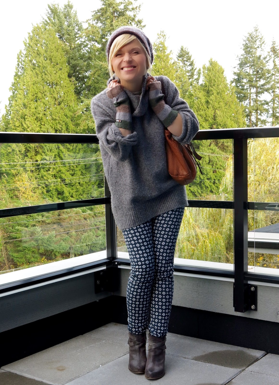 styling an oversized turtleneck with printed skinny pants, booties, and a woolen beanie