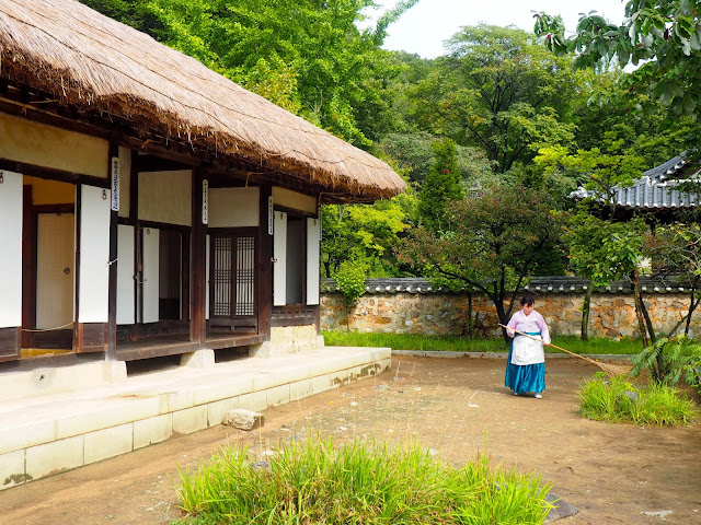 Woman wearing hanbok sweeping outside a traditional style house in the Korean Folk Village, Yongin, Gyeonggi-do, South Korea