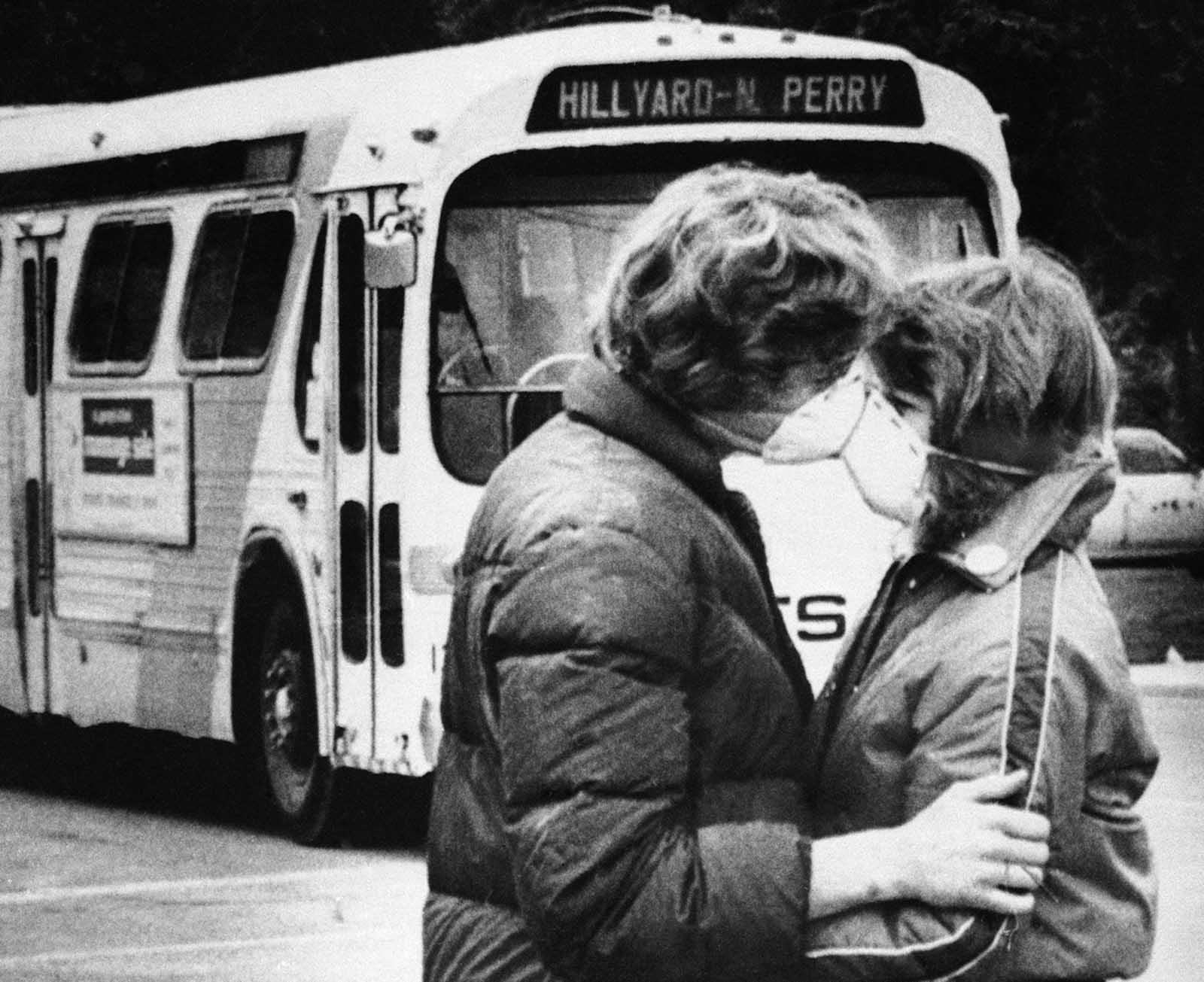 Fifteen-year-old Heidi Havens gives Allen Troup, 16, a kiss as he prepares to board a Spokane City bus, on May 27, 1980. Spokane residents had to wear face masks while outside for days after the eruption because of possible health threats from volcanic ash sprayed over the area by Mount St. Helens on May 18.