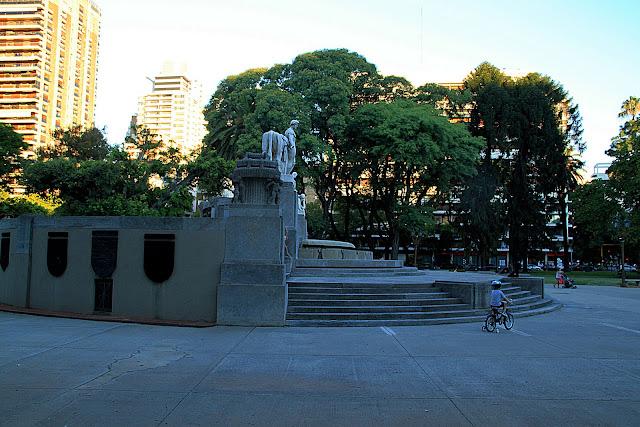 Plaza alemania.Niño en bicicleta frente al monumento