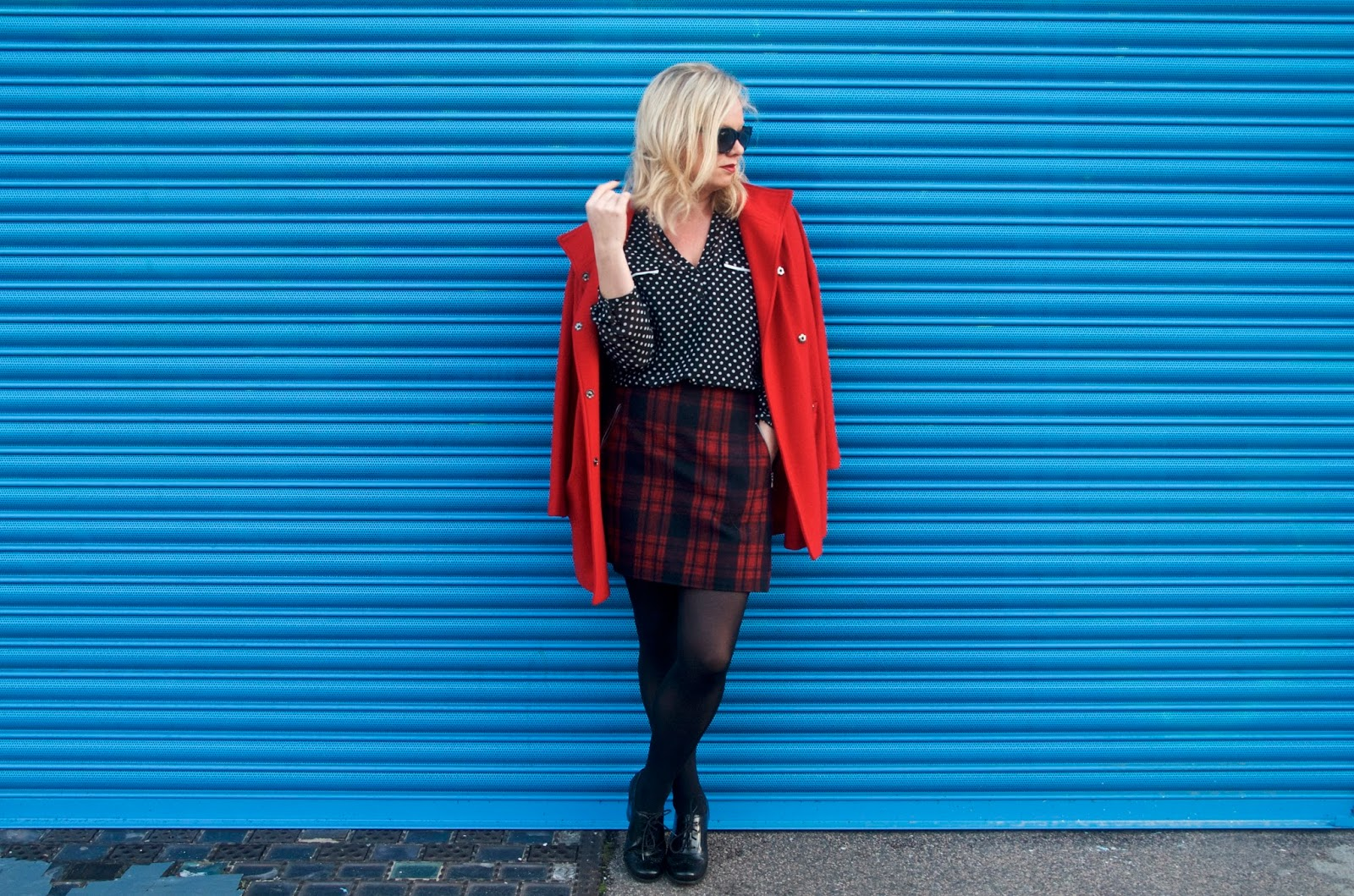 polka dot top, plaid skirt, red coat, tights and brogues with blue wall