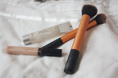 10 Best Beauty Buys of 2013; maybelline fit me concealer, real techniques buffing brush, real techniques face brush, body shop mattifying primer, lying on a bed
