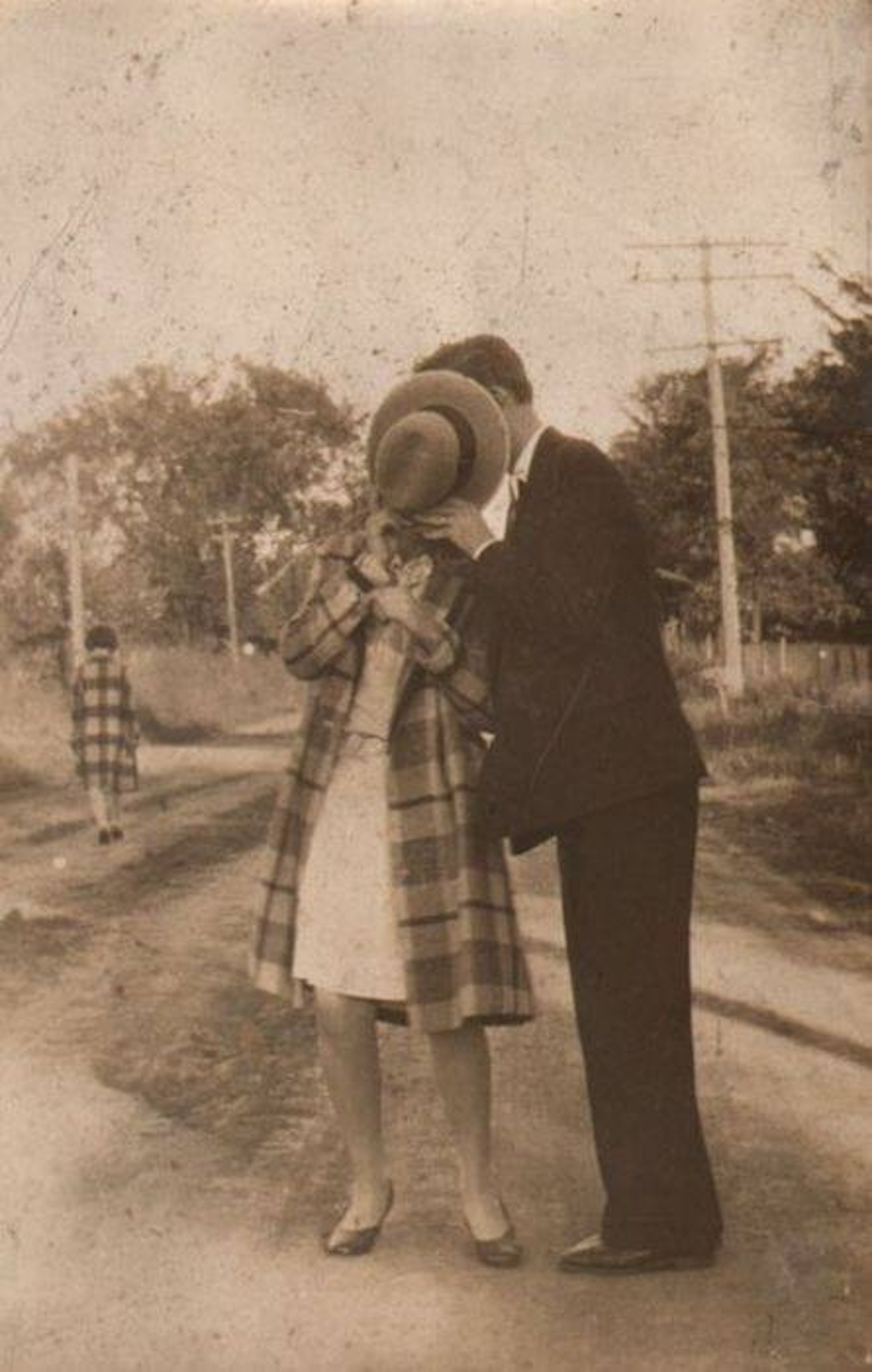 Couple kisses behind a hat. c1940s. Frighten the Horses. marchmatron.com