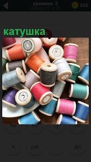 На столе разбросаны несколько разнообразных катушек с цветными нитками