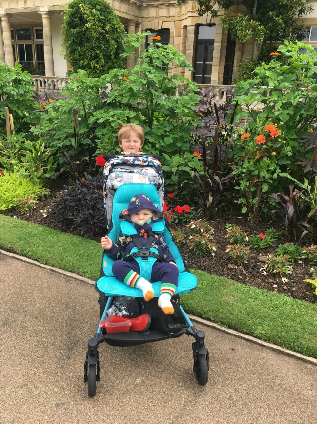 boy-stood-behind-stroller-in-front-of-stately-home
