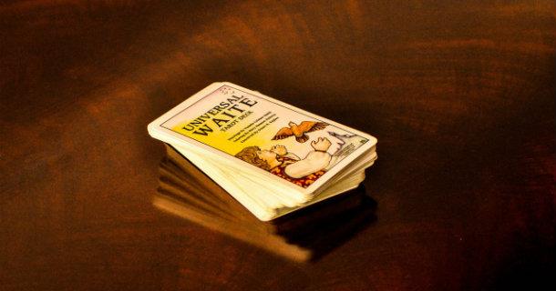 Un jeu de tarot divinatoire en anglais posé sur une table de bois sombre