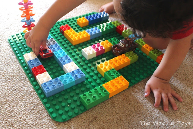 Child playing with a Duplo car maze