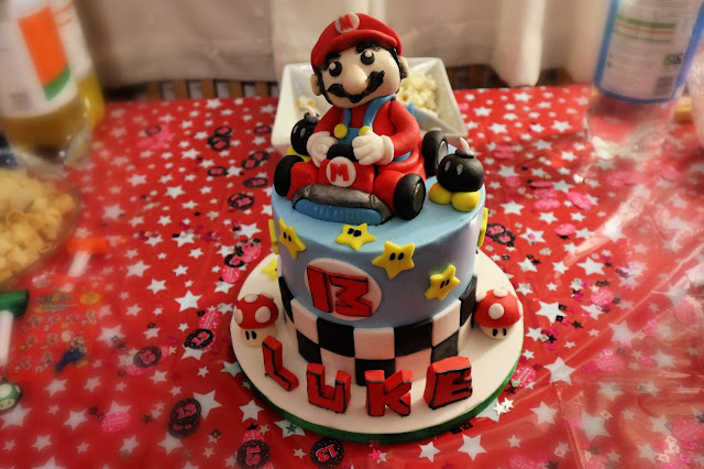 A cake with MarioKart decorations and a Super Mario figure, made of icing, seated on top in a car.