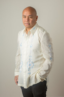 Photo of Patrick Rosal. Image of a bald Asian man with a neutral expression standing in front of a beige wall. He wears a cream colored long sleeve button up shirt with light blue embroidery down the front.