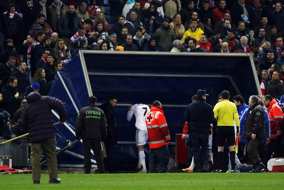 Cristiano Ronaldo grabs his head after being hit with a lighter upon leaving the field