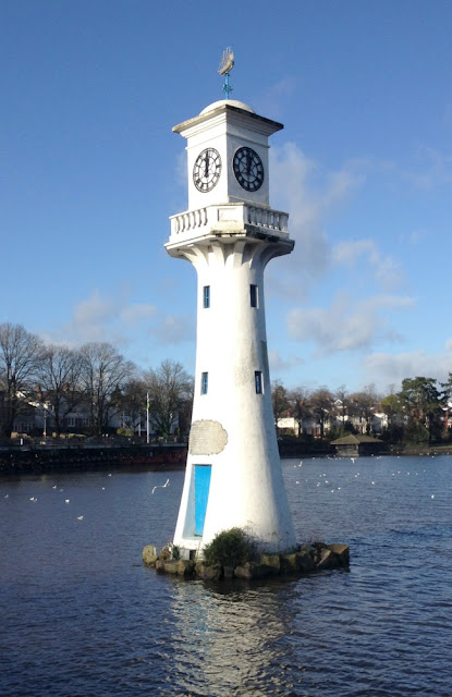 Picture of a lighthouse in a lake with a clock on each side