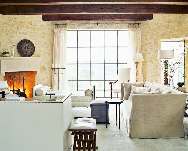 Living room with exposed beams, a large fireplace, a stone wall, large encasement window, taupe sofa and matching bench