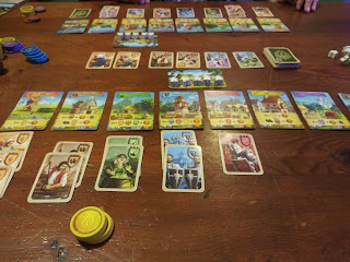 A game of Majesty: For the Realm in progress. The photo is taken from the point of view of one player, looking at his tableau. The location cards are laid out in front of him, with three millers, two brewers, two witches, two guards, and one knight under their respective location cards. A stack of yellow coin tokens sits nearby. Above the location cards, the worker card holds five meeples. The row of character cards is above that. In the background, the other player's tableau can be seen. A variety of coin tokens in various colours can be seen off to one side. A pile of white meeples can be seen on the other side.