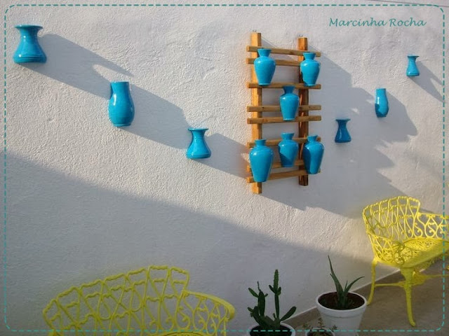 vasos de cerâmica pintados de azul decoram o muro