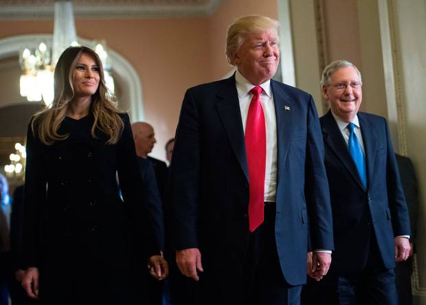 Donald Trump and his wife Melania walk with Senate Majority Leader Mitch McConnell (R) following a meeting at the Capitol in