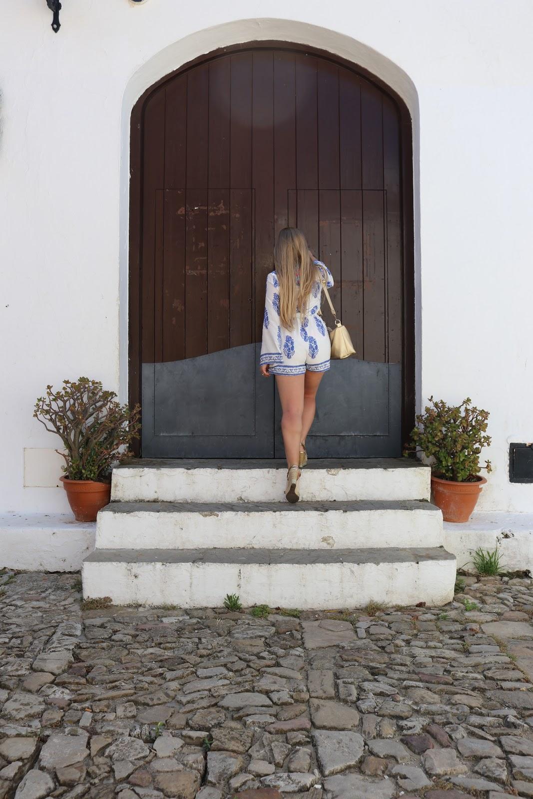 Blonde girl, Katie Heath wearing blue and white playsuit from Quiz in Castillo de Castellar, Spain