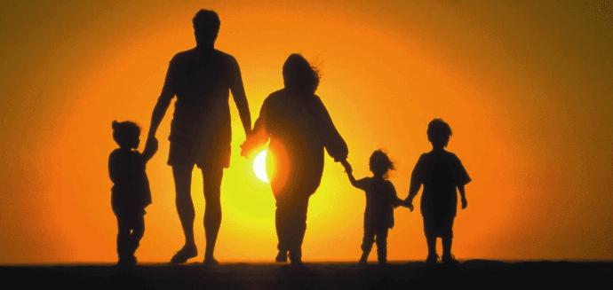 família caminhando ao por do sol