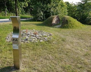 Archäologiepark Altmühltal bei der Schleuse Haidhof: hinten ein aufgeschnittener Grabhügel mit zwei übereinanderliegenden Bestattungen, vorne die Andeutung einer Kinderbestattung mit Beigabe eines Kegelhalsgefäßes