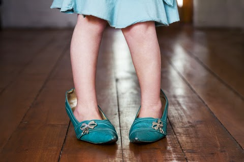 A child wearing her mother's high-heeled shoes