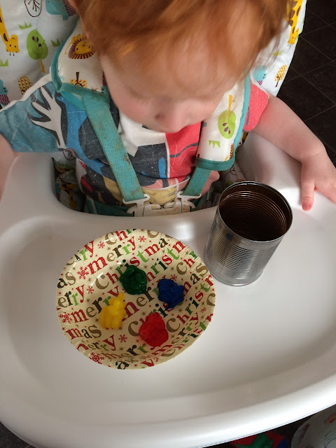 Toddler in a highchair with the can and paint, waiting to start