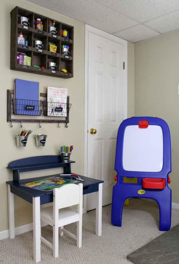 Organized art station for kid's art and craft supplies: Desk, chair, easel, and hanging supply storage
