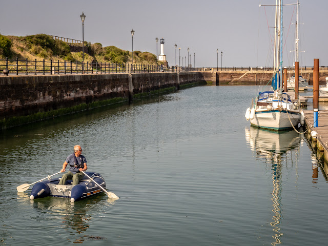 Photo of Phil rowing our dinghy down to the far end of the marina