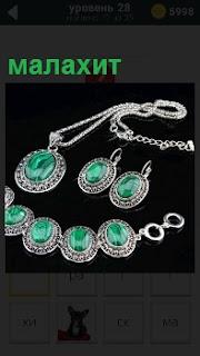 На черном фоне изображены изделия из малахита, кулон, серьги и ожерелье