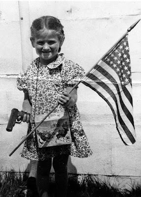 Little girl holding a gun and the American flag picture