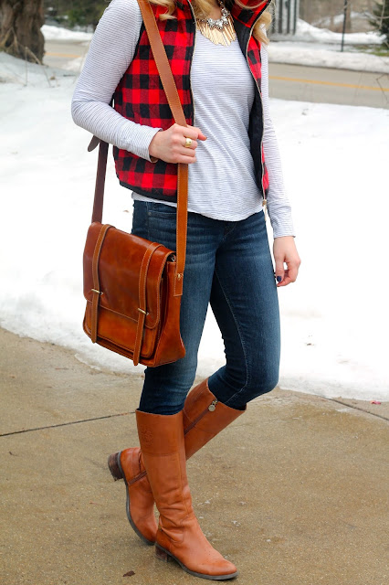red plaid vest layered over striped top with jeans and riding boots