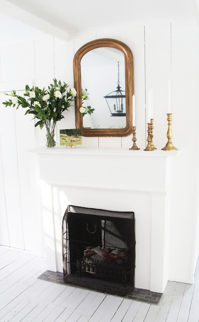 a country farmhouse ktichen fireplace white floors, louis mirror mantel, brass candlesticks, candle and a bouquet
