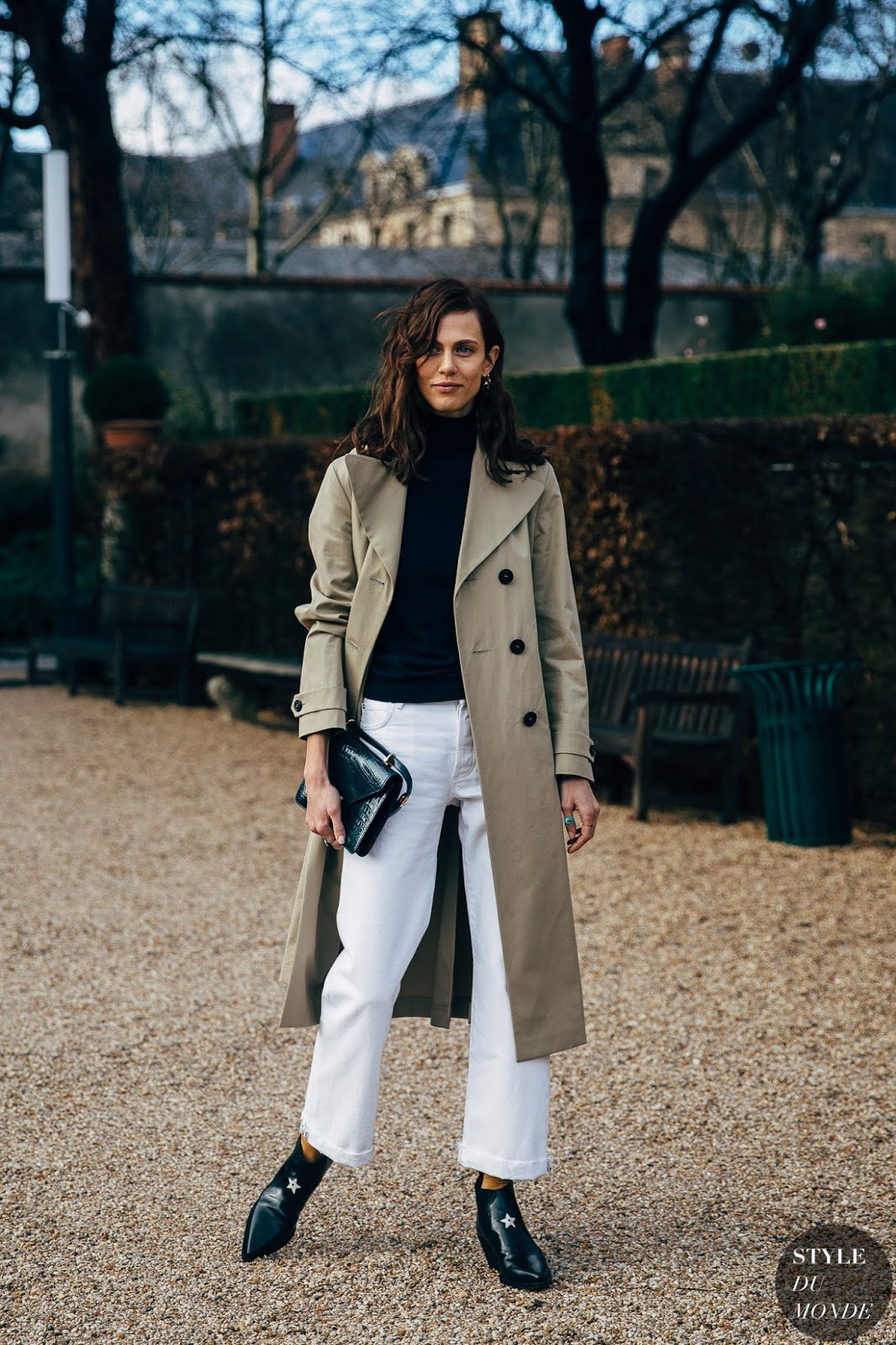 Transitional Spring Outfit Idea: Model Aymeline Valade in a trench coat, black turtleneck sweater, cropped wide-leg jeans, and black pointed-toe ankle boots