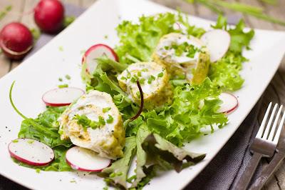 Ei-Schnittlauch-Rolle mit Krentopfen auf Blattsalat