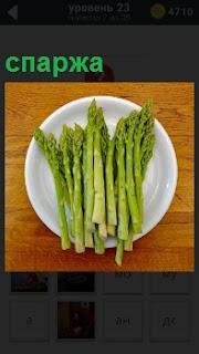 На тарелке на столе лежит травянистое растение спаржа, готовое к приготовлению
