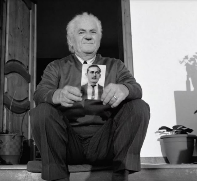 Sazan Hoxha with the portrait of his father
