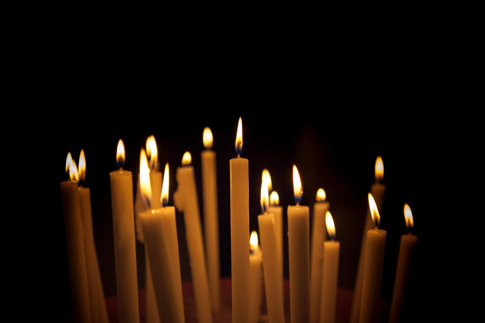 21 white taper candles lit in the dark, against a pitch black background
