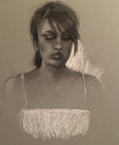 Charcoal drawing of woman in a white sundress looking down drawn on dark blue paper