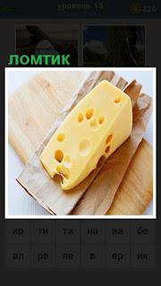 на разделочной доске лежит небольшой ломтик сыра с дырочками