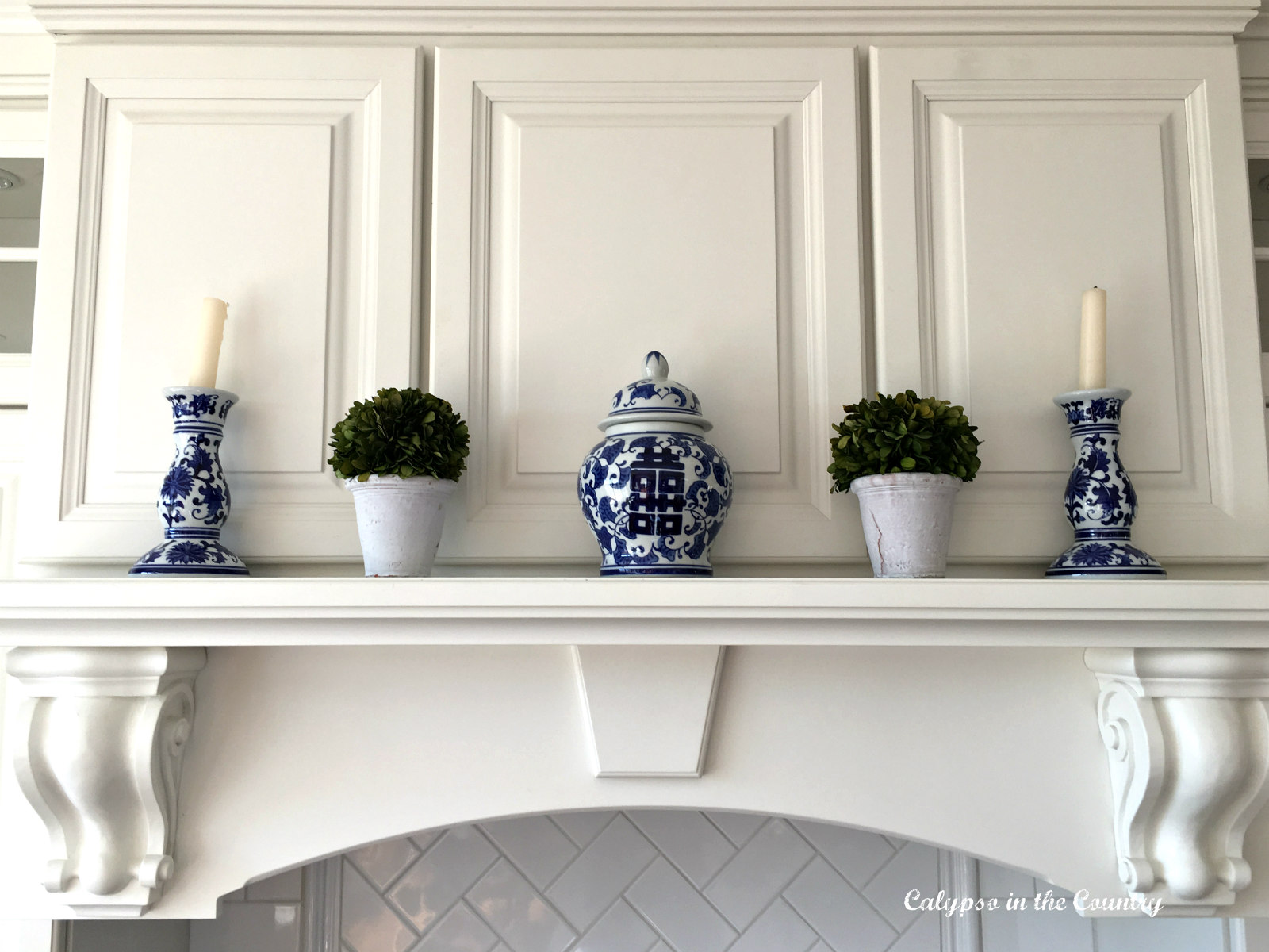 Blue and white accessories on stove mantel