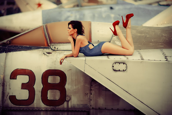 Contaplative girl in blue swinsuit and red high heels lies atop an abandoned Soviet jet fighter in an aircraft graveyard