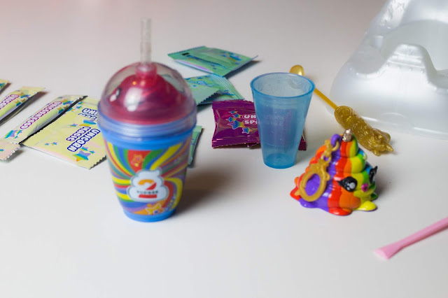 The contents of the surprises in Poopsie Surprise Unicorn including a drinking cup, keychain and Unicorn food