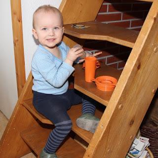 Christkind spielt an Treppe