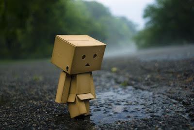 Muñeco de cartón en la carretera mojada