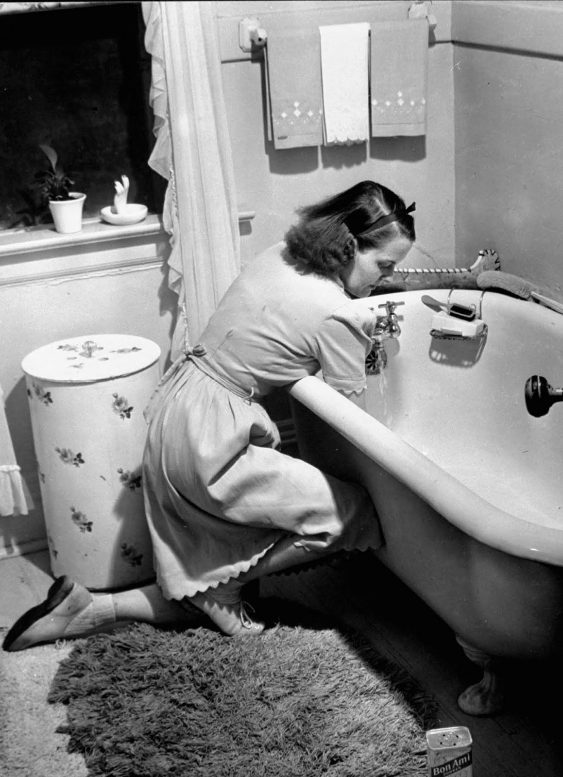 Jane scrubbing the bathtub in bathroom at home.