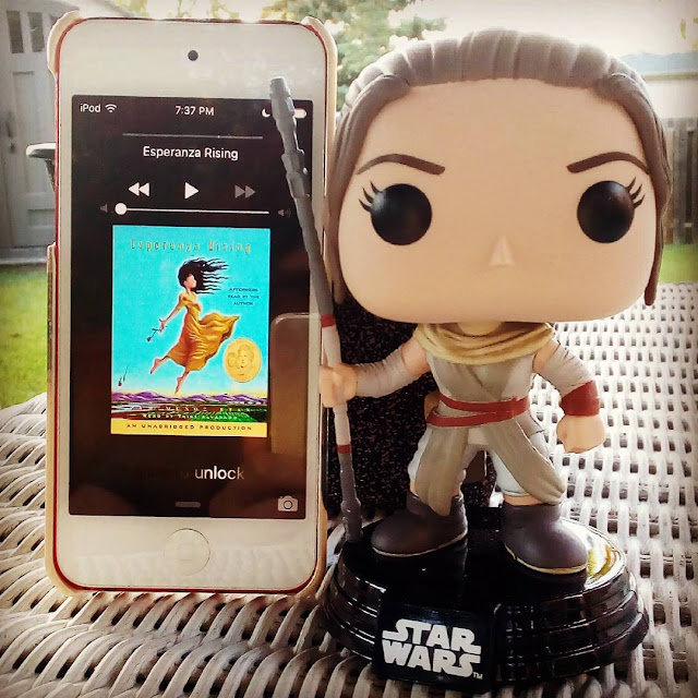 A large-headed Funko Pop of Rey from Star Wars stands next to a white iPod with Esperanza Rising's cover on its screen. The cover features a Mexican girl wearing a yellow dress. She floats into the air, arms stretched out behind her.