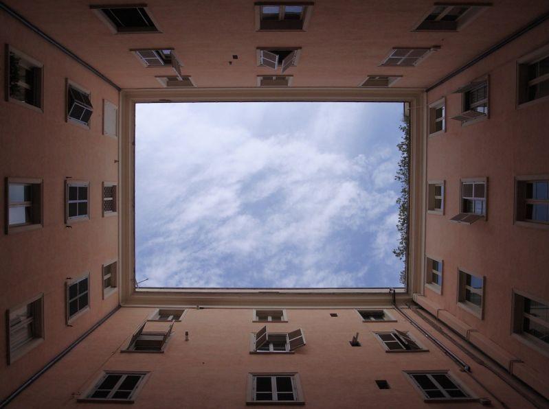 Blick aus einem Innenhof hinauf in den freien Himmel
