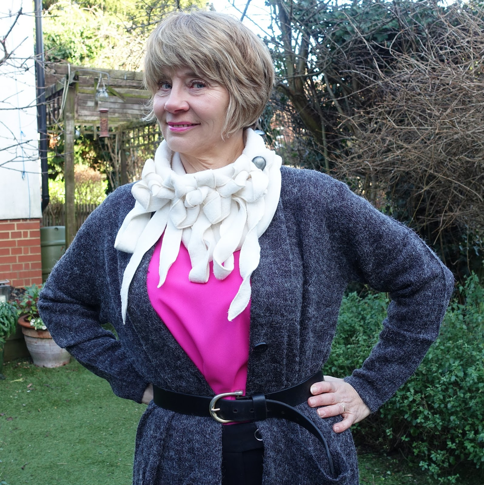 Image showing a middle aged fashionista in long line grey knit cardigan black trousers pink top and elaborate cream neck wear.